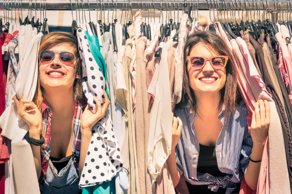 Two young women smiling through rack of clothes